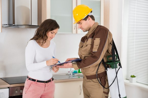 Woman giving review to pest control man